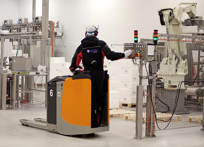 Robotarmer behandler kassene før de flyttes videre med truck.